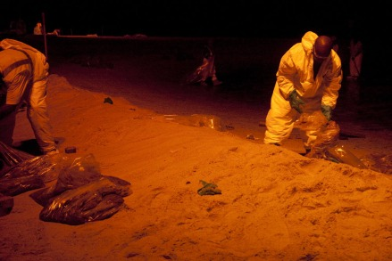 Long Beach, Mississippi, July 7, 2010. A large amount of oil washed ashore in Long Beach prompting the first night time cleaning. Lights were brought in for the workers, originally, the lights had amber colored filters on them to protect any sea turtles in the area. The filters were peeled off when the men in charge were told there was no danger from the lights.  Photo by: Jenn LeBlanc/Iris Photo Agency
